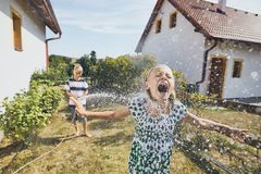 Children having fun with splashing water. Siblings on the back yard of the house during summer day stock photography