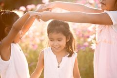 Children having fun to play together in the cosmos flower field Stock Photos