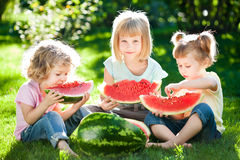 Children having picnic. Group of happy children eating watermelon outdoors in spring park