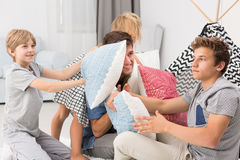 Children having pillow fight. Children and their father having pillow fight royalty free stock images