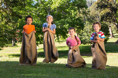 Children having a sack race in park Stock Images