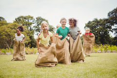 Children having a sack race. In park on a sunny day Stock Image