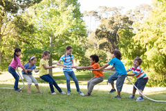 Children having a tug of war in park. On a sunny day Stock Photo