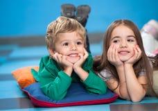 Children With Head In Hands Lying On Floor In. Cute preschool children with head in hands lying on floor in classroom stock images