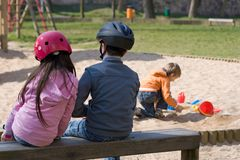 Children with Helmets. Two children on bench with helmets.  Third  child without helmet plays in sand Stock Image