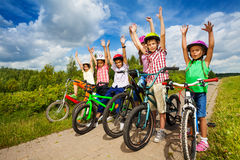 Children with helmets sit on their bikes in a row Royalty Free Stock Photos