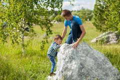 Children help each other to climb the rock royalty free stock photos