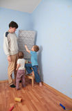 Children Help Father To Glue Wall-papers Royalty Free Stock Photo