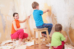 Children help mother remove old wallpapers Stock Photo
