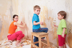 Children help mother remove old wallpapers from wa stock image