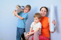 Children help mothrer to glue wall-papers Royalty Free Stock Photos