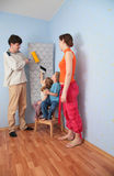 Children help parents to glue wall-papers Stock Photo