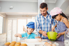 Children helping father in preparing food. At home Stock Photo