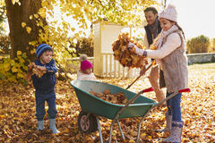 Children Helping Father To Collect Autumn Leaves In Garden Royalty Free Stock Images