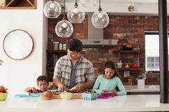 Children Helping Father To Make School Lunches In Kitchen At Home stock photos