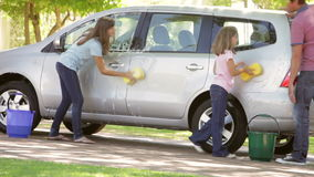 Children Helping Father To Wash Car. Two girls washing car in driveway using sponge and bucket as father watches. Shot on Canon 5D MkII at 25fps stock video footage