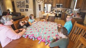 Children helping grandma tie a quilt at the dining table