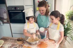 Children helping mother in the kitchen baking together. Home activities with kids Stock Images