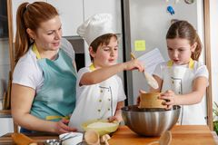 Children helping mother in the kitchen baking together. Home activities with kids stock image