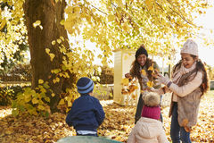 Children Helping Mother To Collect Autumn Leaves In Garden Royalty Free Stock Photo