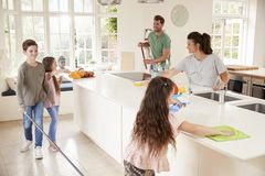 Children Helping Parents With Household Chores In Kitchen royalty free stock photos