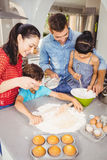 Children helping parents in preparing food. At home Stock Photos
