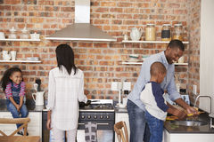 Children Helping Parents To Prepare Meal In Kitchen Stock Images