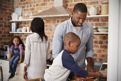 Children Helping Parents To Prepare Meal In Kitchen Stock Photos