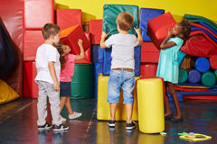 Children helping to tidy up in preschool gym royalty free stock photography