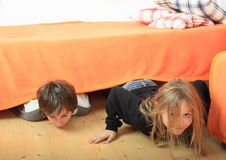 Children hiding under bed. Hairy child - smiling blond girl and her brother hiding under orange cover of bed while lying on wooden floor Stock Photo