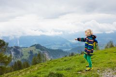 Children hiking in Alps mountains. Kids outdoor. Children hiking in Alps mountains. Kids look at snow covered mountain in Austria. Spring family vacation Stock Image