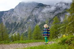 Children hiking in Alps mountains. Kids outdoor. Children hiking in Alps mountains. Kids look at snow covered mountain in Austria. Spring family vacation Stock Images