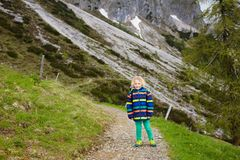 Children hiking in Alps mountains. Kids outdoor. Children hiking in Alps mountains. Kids look at snow covered mountain in Austria. Spring family vacation Stock Photos