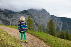 Children hiking in Alps mountains. Kids outdoor. Children hiking in Alps mountains. Kids look at snow covered mountain in Austria. Spring family vacation Royalty Free Stock Images
