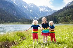 Children hiking in flower field at mountain lake stock photos