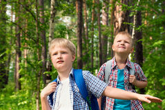 Children hiking outdoor. Children with backpacks walking in a summer forest, go hiking and having fun outdoor Royalty Free Stock Photo