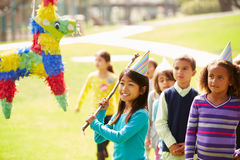 Children Hitting Pinata At Birthday Party Stock Photos