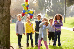 Children Hitting Pinata At Birthday Party Royalty Free Stock Images