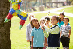 Children Hitting Pinata At Birthday Party Stock Photography