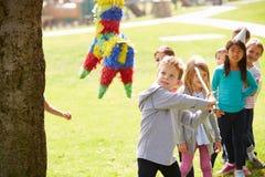 Children Hitting Pinata At Birthday Party Stock Image