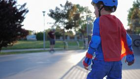 Children hobby, small boy in superhero suit spends free time on playground stock video
