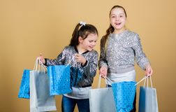 Children hold bunch packages. Kids fashion. Expect more. Pay less. Girls sisters friends with shopping bags beige. Background. Shopping and purchase. Black royalty free stock images
