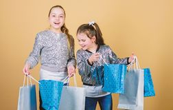 Children hold bunch packages. Kids fashion. Expect more. Pay less. Girls sisters friends with shopping bags beige. Background. Shopping and purchase. Black royalty free stock photography