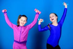 Children hold dumbbells blue background. Sport for teens. Easy exercises with dumbbell. Sporty upbringing. On way to. Stronger body. Girls exercising with stock photos