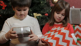 Children hold gift boxes in their hands. Little children holding gift boxes in their hands near the christmas tree. Little caucasian kids turning their gifts in stock footage