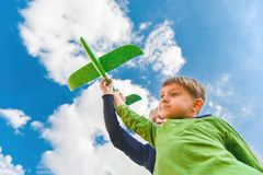 Children hold a green plane in their hands against a blue sky in the clouds; concept of tourism, travel and freedom.  stock photo