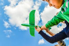 Children hold a green plane in their hands against a blue sky in the clouds; concept of tourism, travel and freedom stock photos