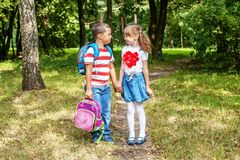 Children hold hands. The boy is carrying a backpack to a girl. T