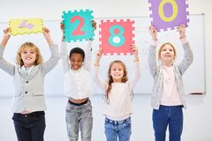Children hold up signs with numbers. Children in elementary school hold up numbers signs as a teambuilding exercise stock photos