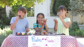 Children Holding Bake Sale. Three children at bake sale stall eating cakes.Shot on Canon 5D MkII at 25fps stock footage